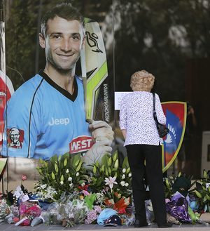 A woman is seen lying flowers amongst other tributes next to a photograph of Phil Hughes outside the Adelaide Oval