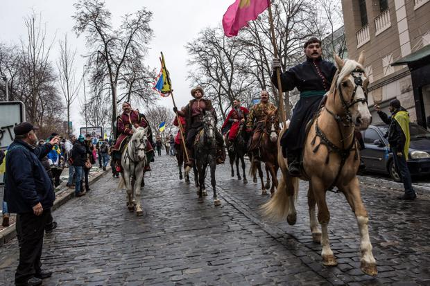 KIEV, UKRAINE - DECEMBER 8: Men dressed as Cossacks ride horses through the streets on December 8, 2013 in Kiev, Ukraine. Thousands of people have been protesting against the government since a decision by Ukrainian president Viktor Yanukovych to suspend a trade and partnership agreement with the European Union in favor of incentives from Russia. (Photo by Brendan Hoffman/Getty Images)