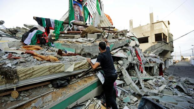 A Palestinian walks on the rubble of the house of the top Hamas leader in Gaza, Ismail Haniyeh, hit by a pre-dawn Israeli strike, in Gaza City, northern Gaza Strip, Tuesday, July 29, 2014. Early Tuesday, Israel warplanes struck a series of targets in Gaza City, including Haniyeh's house and government offices, while Gaza's border area with Israel was hit by heavy tank shelling. (AP Photo/Lefteris Pitarakis)