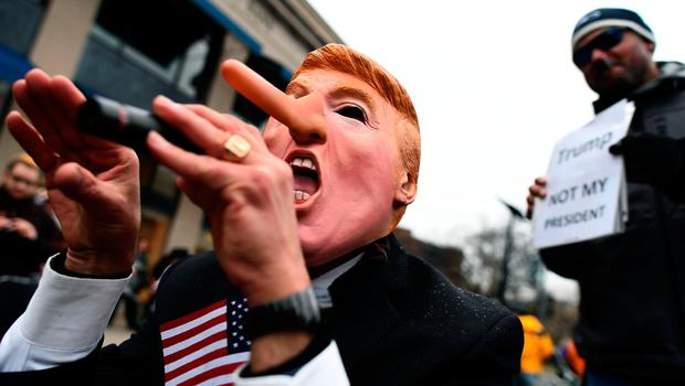 Demonstrators protest against US President-elect Donald Trump before his inauguration on January 20, 2017, in Washington, DC.         Donald Trump will be sworn in as the 45th president of the United States Friday -- capping his improbable journey to the White House and beginning a four-year term that promises to shake up Washington and the world. / AFP PHOTO / Jewel SAMADJEWEL SAMAD/AFP/Getty Images