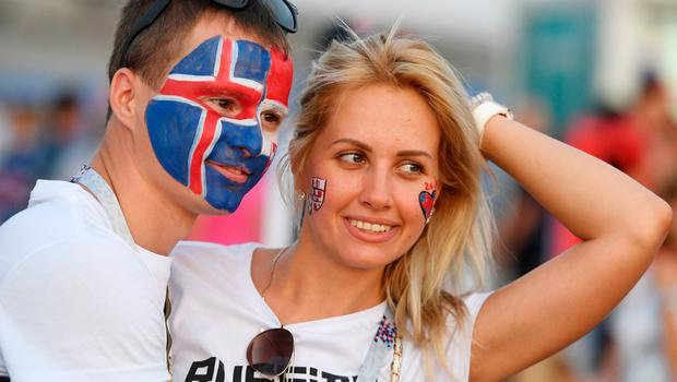 A fan with half his face painted with the Icelandic flag and the other half with the Croatian one poses with another fan before the Russia 2018 World Cup Group D football match between Iceland and Croatia at the Rostov Arena in Rostov-On-Don on June 26, 2018.