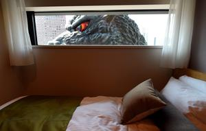 "A life-size Godzilla head is seen through a window of the ""Gozilla View Room"" of Hotel Gracery Shinjuku at Kabukicho shopping district in Tokyo on April 9, 2015. The Godzilla is a main feature of the new commercial complex comprising a 970-room hotel, movie theathres and restaurants which will be open this month.    AFP/Getty Images"