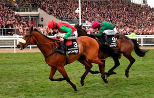 CHELTENHAM, ENGLAND - MARCH 11:  Dodging Bullets ridden by Sam Twiston-Davies passes in front of the grandstand ahead of Somersby ridden by Brian Hughes to win the Betway Queen Mother Champion Chase during Ladies Day at the Cheltenham Festival at Cheltenham Racecourse on March 11, 2015 in Cheltenham, England.  (Photo by Alex Livesey/Getty Images)