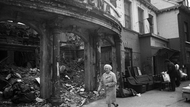 This lady is walking past what had been the Clonard Picture House on the Falls Road (opened in 1913), with the remains of the foyer swept back in off the pavement. Note the black flag, which was part of the campaign over the Republican prisoners, and the furniture for sale, which may have been a result of people losing their homes.