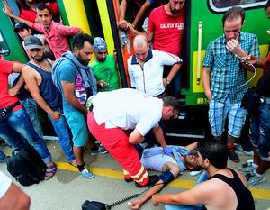 A rescuer helps a migrant lying on the platform outside a local train coming from Budapest and heading to the Austrian border, that has been stopped in Bicske by authorities, west of the Hungarian capital on September 3, 2015. The train carrying between 200 and 300 migrants left Budapest's main international train station after authorities re-opened the station to migrants as the EU is grappling with an unprecedented influx of people fleeing war, repression and poverty in what the bloc has described as its worst refugee crisis in 50 years.   AFP PHOTO / ATTILA KISBENEDEKATTILA KISBENEDEK/AFP/Getty Images
