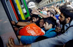 TOPSHOTS Migrants of several countries enter a local train with direction to the Hungarian-Austrian border at Keleti (East) railway station in Budapest on September 3, 2015. A train carrying between 200 and 300 migrants left Budapest's main international train station and headed toward the Austrian border, after authorities re-opened the station to migrants.  AFP PHOTO / PETER KOHALMIPETER KOHALMI/AFP/Getty Images