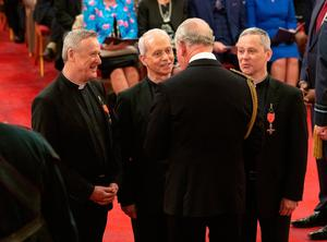 Classical music group the Priests, the Very Reverend David Delargy, the Reverend Eugene O'Hagan and the Reverend Martin O'Hagan are given their MBE (Member of the Order of the British Empire) medals by the Prince of Wales during an investiture ceremony at Buckingham Palace in London.  Pic: Dominic Lipinski/PA Wire