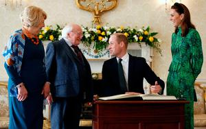 The Duke of Cambridge sings a visitors book next to his wife as they meet with Ireland's President Michael D. Higgins and his wife Sabina, at the official presidential residence Aras an Uachtarain in Dublin, Ireland.