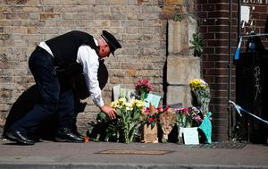 A police officer lays flowers inside a police cordon near the scene in Finsbury Park area of north London after a vehicle was driven into pedestrians, on June 19, 2017. Ten people were injured when a van drove into a crowd of Muslim worshippers near a mosque in London in the early hours of Monday, and a man who had been taken ill before the attack died at the scene. / AFP PHOTO / Tolga AKMENTOLGA AKMEN/AFP/Getty Images