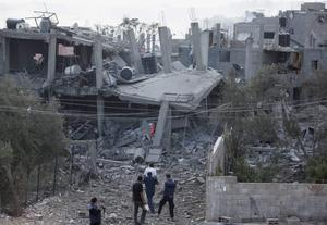 Palestinians and members of the media walk on the rubble of houses, destroyed by Israeli strikes, as they visit the area during a 12-hour cease-fire in Beit Hanoun, northern Gaza Strip, Saturday, July 26, 2014. (AP Photo/Lefteris Pitarakis)