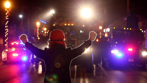 A protester confronts police vehicles with her hands up as police attempt to clear the streets as on November 25, 2014 in Ferguson, Missouri. (Photo by Justin Sullivan/Getty Images)