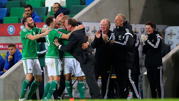 Northern Ireland's Josh Magennis (centre, left) celebrates scoring his side's second goal of the match with teammates during the UEFA European Championship Qualifying match at Windsor Park, Belfast. PRESS ASSOCIATION Photo. Picture date: Thursday October 8, 2015. See PA story SOCCER N Ireland. Photo credit should read: Niall Carson/PA Wire.
