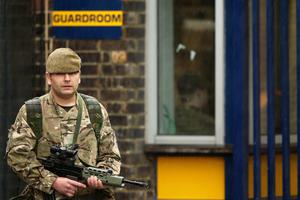 LONDON, ENGLAND - MAY 23: A soldier stands in the rain as security is tightened around Woolwich Barracks on May 23, 2013 in London, England. A British soldier was murdered by suspected Islamists near London's Woolwich Army Barracks yesterday in a savage knife attack. British Prime Minister David Cameron has said that the 'appalling' attack appeared to be terror related. (Photo by Dan Kitwood/Getty Images)