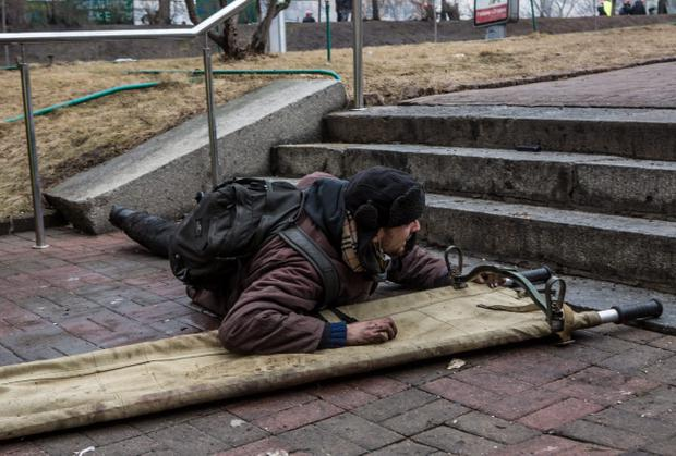 KIEV, UKRAINE - FEBRUARY 20: An anti-government protester takes cover from suspected sniper fire near the Hotel Ukraine on February 20, 2014 in Kiev, Ukraine. After several weeks of calm, violence has again flared between anti-government protesters and police, with dozens killed. (Photo by Brendan Hoffman/Getty Images)