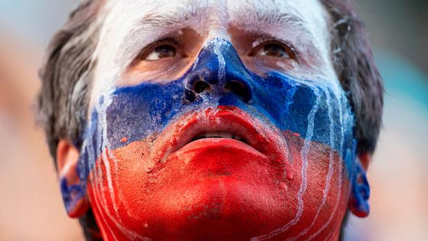 TOPSHOT - A Russia supporter watches the Russia 2018 World Cup Group A football match between Uruguay and Russia on a giant screen at the FIFA Fan Fest in Nizhny Novgorod on June 25, 2018.  / AFP PHOTO / Johannes EISELEJOHANNES EISELE/AFP/Getty Images