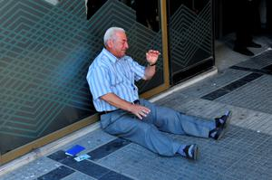 (FILES)-A July 3, 2015 shows Giorgos Chatzifotiadis, sitting on the ground crying outside a national bank branch, as pensioners (unseen) queue to withdraw their pensions, with a limit of 120 euros, in Thessaloniki.  Retiree Giorgos Chatzifotiadis had queued up at three banks in Greece's second city of Thessaloniki in the hope of withdrawing a pension on behalf of his wife, but all in vain.    When he was told at the fourth that he could not withdraw his 120 euros ($133), it was all too much and he collapsed in tears. AFP PHOTO /SAKIS MITROLIDISSAKIS MITROLIDIS/AFP/Getty Images