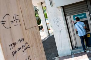 "A man withdraws money from an ATM near graffiti reading ""Euro = Swastika, 1939-1944: 500,000 Greeks dead"" in downtown Athens on July 5, 2015. Greek voters headed to the polls to vote in a historic, tightly fought referendum on whether to accept worsening austerity in exchange for more bailout funds, in a gamble that could see it crash out of the euro. AFP PHOTO / ANDREAS SOLAROANDREAS SOLARO/AFP/Getty Images"