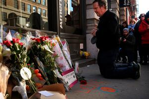 """NEW YORK, NY - JANUARY 11:  People pay tribute to the late musician and performer David Bowie at a memorial outside of the apartment he shared with his wife on January 11, 2016 in New York City. A growing memorial sits outside of the residence in lower Manhattan following news that Bowie died over the weekend following a year long battle with cancer. Bowie was 69 and had just released his 25th studio album, """"Blackstar,"""" to strong reviews on Friday.  (Photo by Spencer Platt/Getty Images) *** BESTPIX ***"""