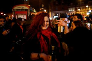 LONDON, ENGLAND - JANUARY 11: A woman dances to a David Bowie song as people celebrate his life at a gathering in Brixton on January 11, 2016 in London, England. British music and fashion icon David Bowie died earlier today at the age of 69 after a battle with cancer. (Photo by Carl Court/Getty Images)