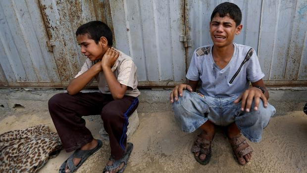 Palestinian youths weep while sitting by the rubble of a home destroyed by an Israeli strike in Khan Younis in the southern Gaza Strip, Friday, July 25, 2014. (AP Photo/Hatem Moussa)