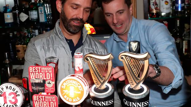 Donald Trump Jr. (left), the son of US President Donald Trump, pours drinks and meets locals in the village of  Doonbeg in Co Clare, on the first day of US President Donald Trump's visit to the Republic of Ireland. PRESS ASSOCIATION Photo. Picture date: Wednesday June 5, 2019. See PA story IRISH Trump. Photo credit should read: Niall Carson/PA Wire