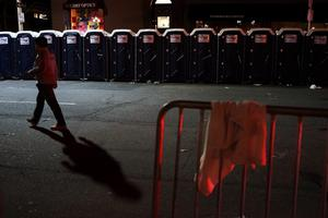 BOSTON, MA - APRIL 16: A man walks by portable toilets near the scene of a twin bombing at the Boston Marathon, on April 16, 2013 in Boston, Massachusetts. Three people are confirmed dead and at least 141 injured after the explosions went off near the finish line of the marathon yesterday. The bombings at the 116-year-old Boston race, resulted in heightened security across the nation with cancellations of many professional sporting events as authorities search for a motive to the violence. (Photo by Spencer Platt/Getty Images)