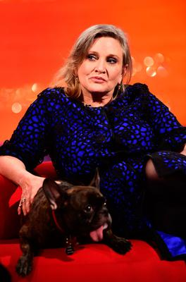 File photo dated 17/12/2015 of Carrie Fisher with her dog Gary during the filming of the Graham Norton Show as the American actress has been rushed to hospital after reportedly suffering a cardiac arrest aboard a flight from London to Los Angeles, TMZ is reporting. PRESS ASSOCIATION Photo. Issue date: Friday December 23, 2016. See PA story SHOWBIZ Fisher. Photo credit should read: Ian West/PA Wire