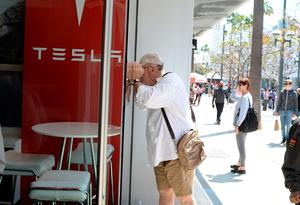 A man looks into the Tesla store in Santa Monica, California, where customers are waiting in line to put a USD 1,000 deposit on the as yet unseen Tesla Model 3, on March 31, 2016.  / AFP PHOTO / ROBYN BECKROBYN BECK/AFP/Getty Images