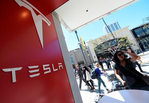 A woman looks into the Tesla store in Santa Monica, California, where customers are waiting in line to put a USD 1,000 deposit on the as yet unseen Tesla Model 3, on March 31, 2016.  / AFP PHOTO / ROBYN BECKROBYN BECK/AFP/Getty Images