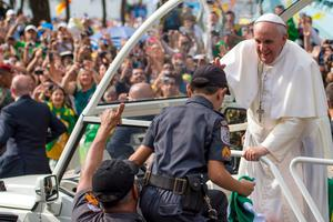 RIO DE JANEIRO, BRAZIL - JULY 28: Pope Francis waves and blesses the son of a policeman from the Popemobile as he arrives to celebrate Mass on Copacabana Beach during World Youth Day celebrations on July 28, 2013 in Rio de Janeiro, Brazil. More than 1.5 million pilgrims are expected to join the pontiff for his visit to the Catholic Church's World Youth Day celebrations which is running July 23-28.  (Photo by Buda Mendes/Getty Images)