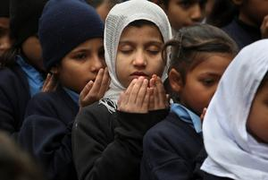 Pakistani students pray during a special ceremony for the victims of Tuesday's school attack in Peshawar, at a school in Lahore, Pakistan, Wednesday, Dec. 17, 2014. Pakistan is mourning as the nation prepares for mass funerals for over 140 people, most of them children, killed in a Taliban attack on a military-run school in the country's northwest. (AP Photo/K.M. Chaudary)