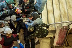 KIEV, UKRAINE - FEBRUARY 20: Medics tend to a gravely wounded anti-government protester in the lobby of the Hotel Ukraine, which has been converted to a medical clinic and makeshift morgue, on February 20, 2014 in Kiev, Ukraine. After several weeks of calm, violence has again flared between anti-government protesters and police, with dozens killed. (Photo by Brendan Hoffman/Getty Images)