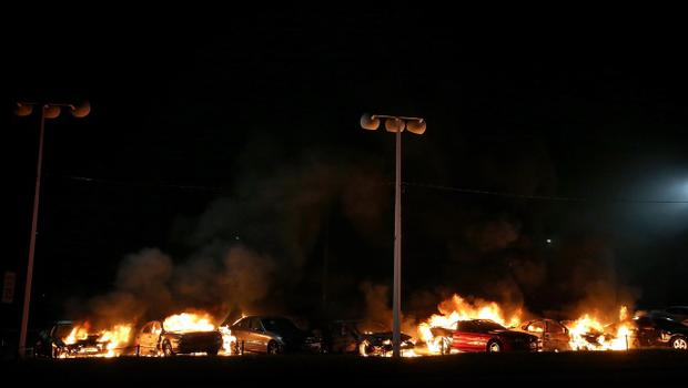 FERGUSON, MO - NOVEMBER 25:  A row of cars burn at a used car lot during a demonstration on November 25, 2014 in Ferguson, Missouri. Ferguson has been struggling to return to normal after Brown, an 18-year-old black man, was killed by Darren Wilson, a white Ferguson police officer, on August 9. His death has sparked months of sometimes violent protests in Ferguson. A grand jury today declined to indict officer Wilson.  (Photo by Justin Sullivan/Getty Images)