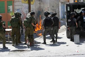 Israeli soldiers gather by flames created from a Molotov cocktail thrown by Palestinians during clashes in Hawara village near the West Bank city of Nablus on Friday, July 25, 2014. (AP Photo/Nasser Ishtayeh)