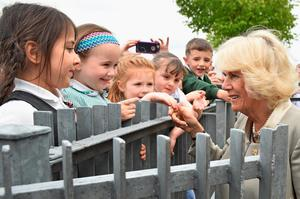 BELFAST, NORTHERN IRELAND - MAY 21:  Camilla, Duchess of Cornwall meets school children as she visits Ballyhackamore Credit Union on May 21, 2015 in Belfast, Northern Ireland. Prince Charles, Prince of Wales and Camilla, Duchess of Cornwall will attend a series of engagements in Northern Ireland following their two day visit in the Republic of Ireland.  (Photo by Jeff J Mitchell - WPA Pool/Getty Images)
