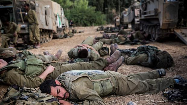 "SDEROT, ISRAEL - JULY 15:  Israeli soldiers sleep next to armored personnel carriers near the Israeli-Gaza border on July 15, 2014 near Sderot, Israel.  As operation 'Protective Edge"" enters it's eighth day of airstrikes by the Israel Defense Forces (IDF) across the Gaza Strip, Egypt has this morning tabled a ceasefire agreement proposing a halting of fighting starting at 9am. Once violence has ceased, the proposal calls for Israel to open a border crossing into Gaza to allow the movement of goods and people. Israel has accepted the Egyptian proposal for a truce, however it is thought Hamas has rejected the deal.  (Photo by Andrew Burton/Getty Images)"