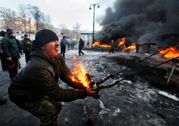 Protesters use a large slingshot to hurl a Molotov cocktail at police in central Kiev, Ukraine, Thursday Jan. 23, 2014. Thick black smoke from burning tires engulfed parts of downtown Kiev as an ultimatum issued by the opposition to the president to call early election or face street rage was set to expire with no sign of a compromise on Thursday. (AP Photo/Sergei Grits)