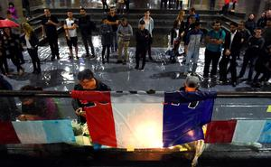 People light candles at a vigil held by the local French community in Sydney on November 14, 2015, as Australians express their solidarity with France following a spate of coordinated attacks that left 128 dead and 180 injured in Paris late on November 13. Both the Opera House and the Sydney Town Hall were bathed in the French colours and New South Wales state Premier Mike Baird said he had also asked for a French flag to fly over the city's famous harbour bridge. AFP PHOTO / William WESTWILLIAM WEST/AFP/Getty Images