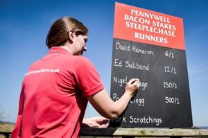 Pennywell Farm VIP Manager Sam Bottoms adjusts the odds in the 2015 Pennywell Bacon Stakes Steeplechase special General Election pig race, featuring Ed Swiliband for the Labour Party, Pork Clegg for the Liberal Democrats, Nigel Forage for Ukip, David Hameron for the Conservative Party and Pork Scratchings representing all other political parties. PRESS ASSOCIATION Photo. Picture date: Tuesday April, 14, 2015. Photo credit should read: Ben Birchall/PA Wire