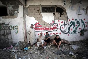 Palestinians sit on debris after seeing their homes destroyed in Israel's military operation on Gaza, during a 12-hour cease-fire in Gaza City's Shijaiyah neighborhood, Saturday, July 26, 2014.  (AP Photo/Khalil Hamra)