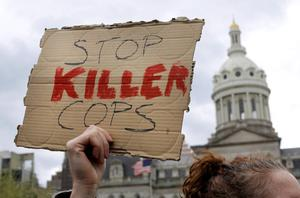 A protestor holds a sign outside of Baltimore's City Hall before a march for Freddie Gray, Thursday, April 23, 2015, in Baltimore. Gray died from spinal injuries about a week after he was arrested and transported in a police van. (AP Photo/Patrick Semansky)