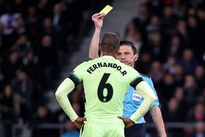 Serbian referee Milorad Mazic gives a yellow card to Manchester City's Brazilian midfielder Fernando during the UEFA Champions League quarter final football match between Paris Saint Germain (PSG) and Manchester City on April 6, 2016 at the Parc des Princes stadium in Paris.  AFP PHOTO / MARTIN BUREAUMARTIN BUREAU/AFP/Getty Images