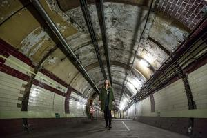 LONDON, ENGLAND - APRIL 13:  A member of staff from the 'London Transport Museum' walks down a tunnel in the Down Street underground station on April 13, 2016 in London, England. London Transport Museum will be giving tours as part of their new 'Hidden London' season beginning May 7, 2016. Down Street station in Mayfair operated between 1907 and 1932 and after closing, played an important part during the Second World War when it was transformed into the Railway Executive Committee's bomb proof shelter. During the height of the Blitz, British Prime Minister Winston Churchill took refuge in the station tunnels.  (Photo by Dan Kitwood/Getty Images)