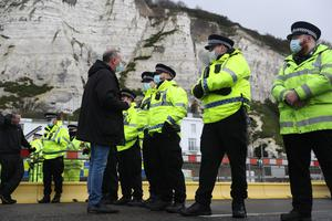 A haulier speaks to police officers blocking the entrance to the Port of Dover (Andrew Matthews/PA)