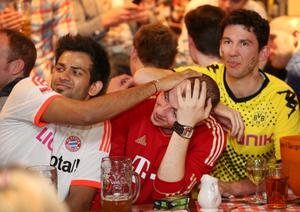LONDON, ENGLAND - MAY 25:  Bayern Munich fans (L and 2L) watch a tv screen in the Bavarian Beerhouse bar with a Borussia Dortmund fan (R) on May 25, 2013 in London, England. Bayern Munich and Borussia Dortmund are playing the Champions League final at Wembley Stadium.  (Photo by Peter Macdiarmid/Getty Images)