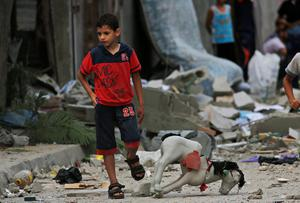 A Palestinian child walks on debris from a destroyed house, following an overnight Israeli strike in Beit Lahiya, in northern Gaza strip, Saturday, July 19, 2014. (AP Photo/Lefteris Pitarakis)