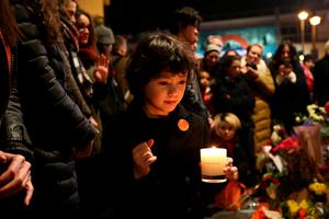 LONDON, ENGLAND - JANUARY 11: A child lays a candle next to a mural of David Bowie in Brixton on January 11, 2016 in London, England. British music and fashion icon David Bowie died earlier today at the age of 69 after a battle with cancer. (Photo by Carl Court/Getty Images)