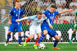 (LtoR) England's forward Wayne Rooney and Iceland's midfielder Gylfi Sigurdsson vie for the ball during the Euro 2016 round of 16 football match between England and Iceland at the Allianz Riviera stadium in Nice on June 27, 2016. / AFP PHOTO / BERTRAND LANGLOISBERTRAND LANGLOIS/AFP/Getty Images