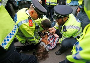 Police officers arrest a demonstrator during a protest against the visit of Israel's Prime Minister Benjamin Netanyahu to Britain, in front of Downing Street in London, Wednesday, Sept. 9, 2015. (AP Photo/Frank Augstein)