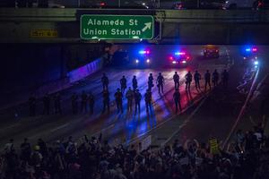 LOS ANGELES, CA - NOVEMBER 09: Police advance on protesters who shut down the 101 freeway in opposition to the upset election of Republican Donald Trump over Democrat Hillary Clinton in the race for President of the United States on November 9 2016 in Los Angeles, California, United States.   (Photo by David McNew/Getty Images)